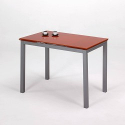 Mesa de cocina de cristal naranja con alas extensibles.